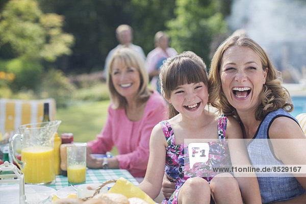 Mehrgenerationen-Familie lacht bei Tisch im Hinterhof