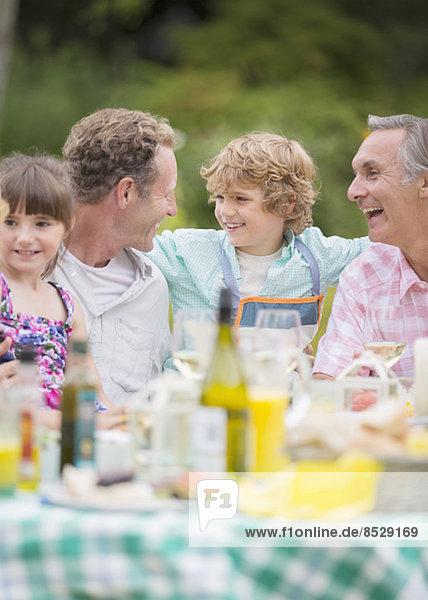 Familie genießt das Mittagessen am Tisch im Freien
