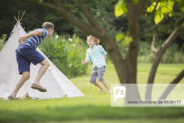 Vater jagt den Sohn um das Tipi im Hinterhof.