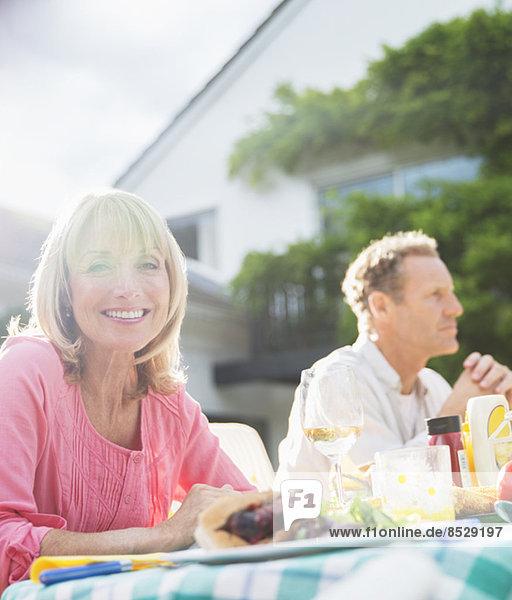 Lächelnde Frau bei Tisch im Hinterhof