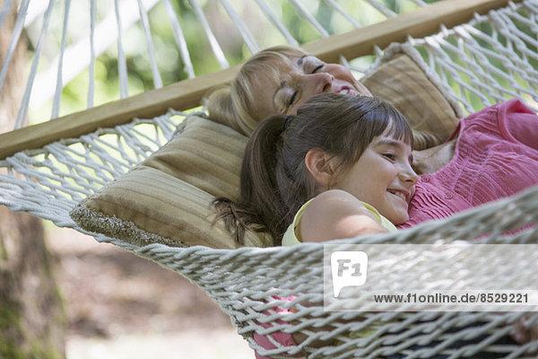 Frau und Enkelin entspannen in der Hängematte