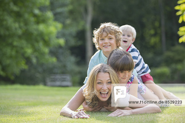 Children laying on mother in grass