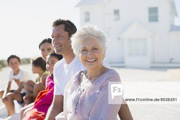 Mehrgenerationen-Familie lächelt vor dem Strandhaus