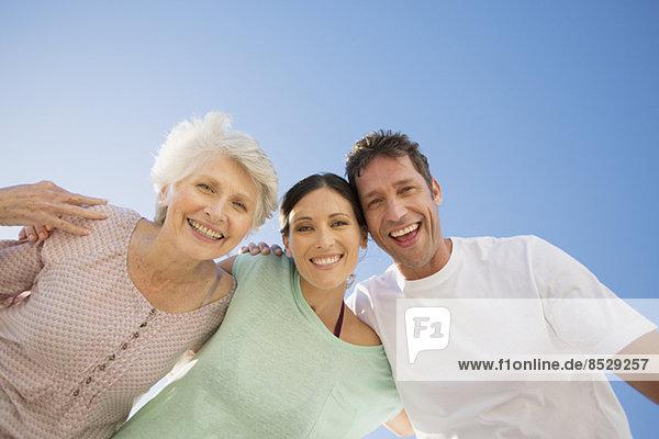 Seniorenfrau umarmt Paar gegen blauen Himmel