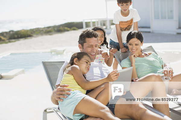 Familie mit digitalem Tablett auf dem Liegestuhl am Pool