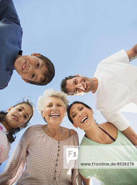 Mehrgenerationen-Familie lächelt vor blauem Himmel