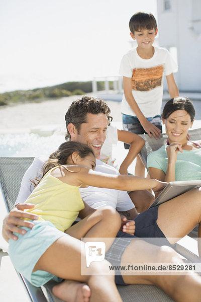 Familie mit digitalem Tablett auf Liegestühlen am Pool