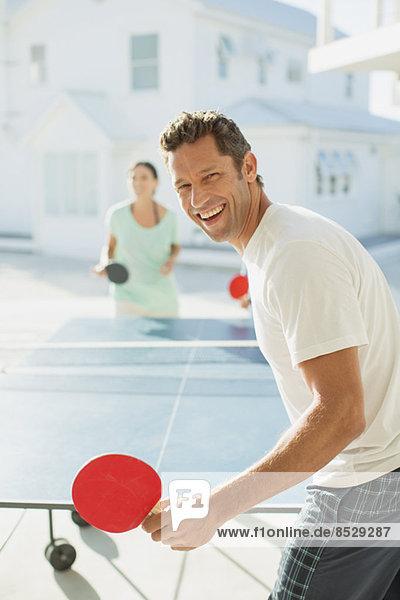 Pärchen spielen Tischtennis im Freien