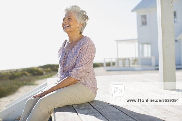 Seniorin auf Deck vor dem Strandhaus sitzend