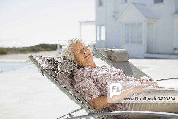 Seniorin schläft auf einem Liegestuhl am Pool