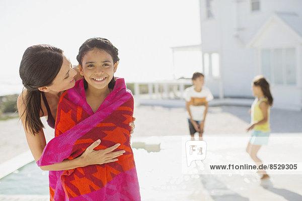 Mutter wickelt Tochter in Handtuch am Pool ein