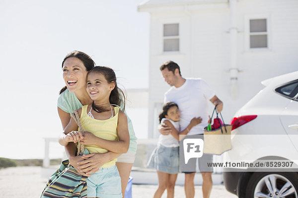 Familienumarmung in sonniger Einfahrt