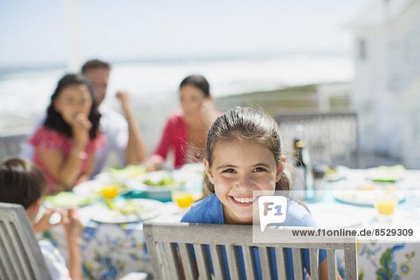 Lächelndes Mädchen am Tisch auf der Sonnenterrasse