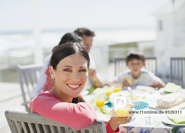 Frau trinkt Orangensaft am Tisch auf der Sonnenterrasse