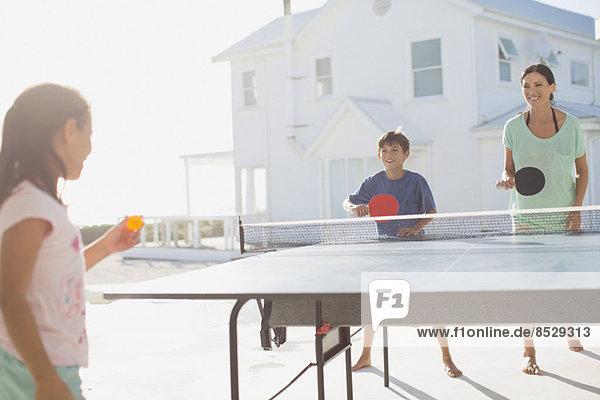 Familie beim gemeinsamen Tischtennisspielen vor dem Haus