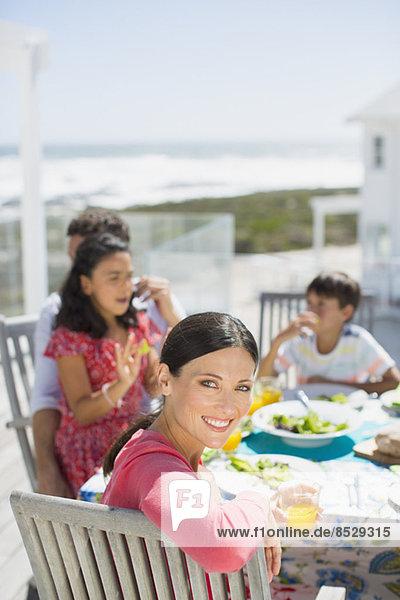 Familienessen am Tisch auf der sonnigen Terrasse mit Blick auf den Ozean