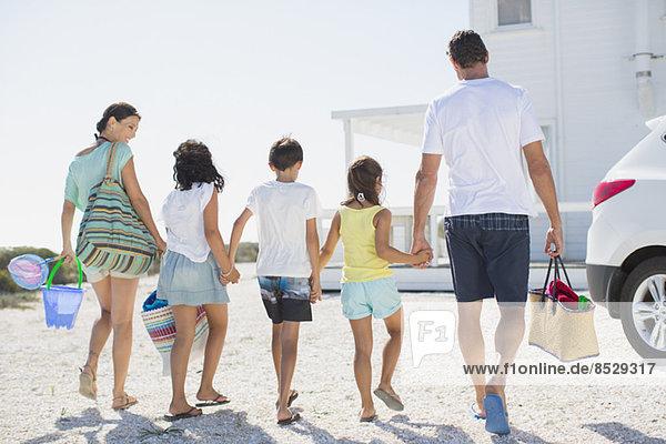 Familie hält sich an den Händen und trägt Strandkleidung in der sonnigen Einfahrt.