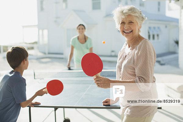 Mehrgenerationen-Familie beim Tischtennisspielen vor dem Strandhaus