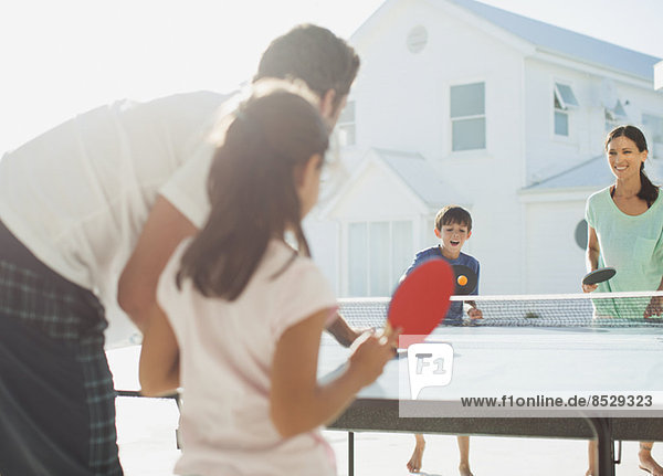 Familie spielt Tischtennis außerhalb des Hauses
