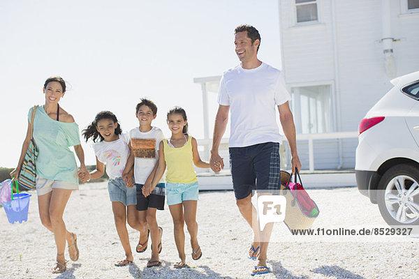 Familie beim Händchenhalten und Wandern mit Strandkleidung in sonniger Einfahrt