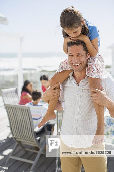 Vater trägt Tochter auf Schultern auf sonniger Terrasse