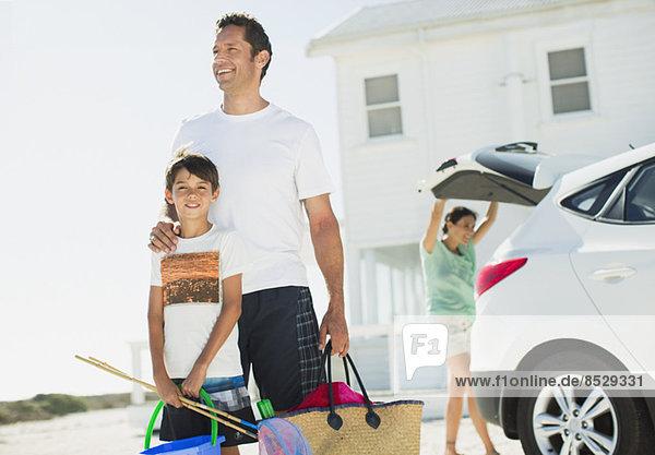 Vater und Sohn umarmen sich vor dem Auto in der sonnigen Einfahrt