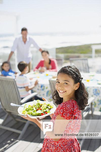 Lächelndes Mädchen mit Salatschüssel auf sonniger Terrasse