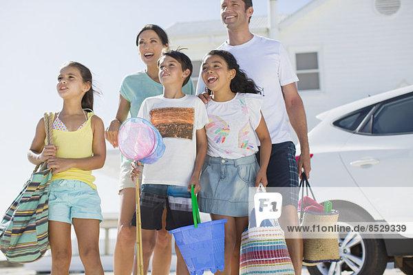 Familienstand mit Strandkleidung in sonniger Einfahrt