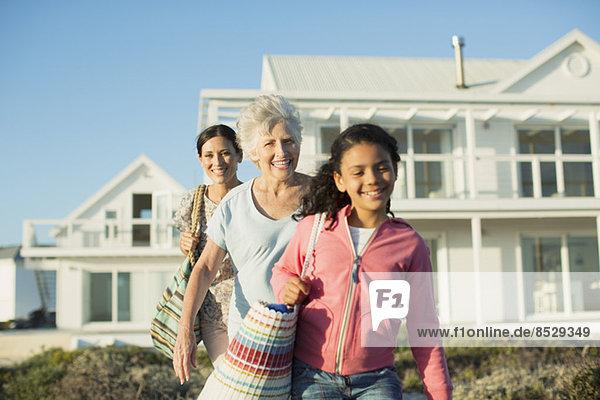 Mehrgenerationen-Frauen beim Spaziergang am Strand vor dem Haus