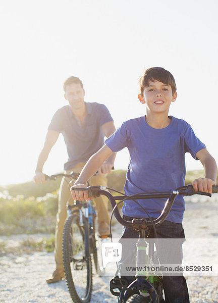 Vater und Sohn beim Fahrradfahren am sonnigen Strand