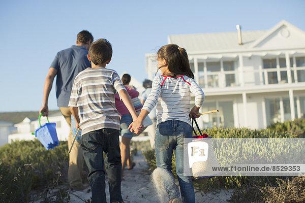 Bruder und Schwester halten sich am Strandweg an den Händen.