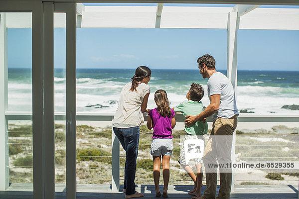 Familie genießt Meerblick von der Terrasse aus