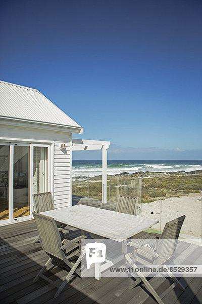 Tisch und Stühle auf der Terrasse mit Blick auf den Strand