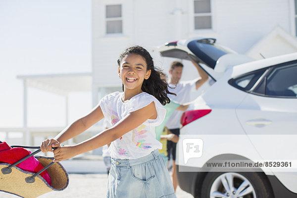 Fröhliches Mädchen schwingt Strandtasche vor dem Auto in sonniger Auffahrt