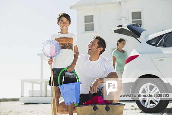 Vater und Sohn halten Strandkleidung vor dem Auto in der sonnigen Einfahrt.