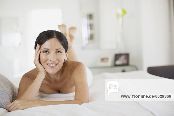 Lächelnde Frau auf dem Bett liegend