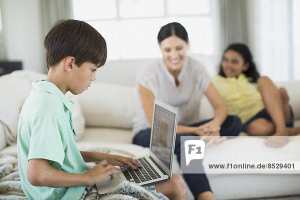 Junge mit Laptop auf Sofa im Wohnzimmer