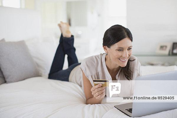 Frau online einkaufen mit Laptop