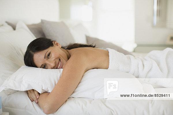 Frau umarmt Kissen auf dem Bett