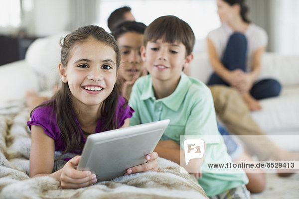 Kinder mit digitalem Tablett auf dem Sofa im Wohnzimmer