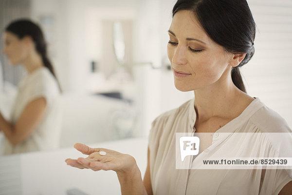 Frau nimmt Pille im Bad