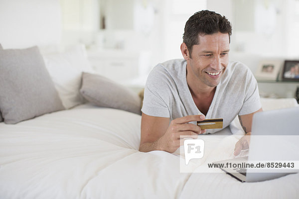 Man shopping online with laptop on bed