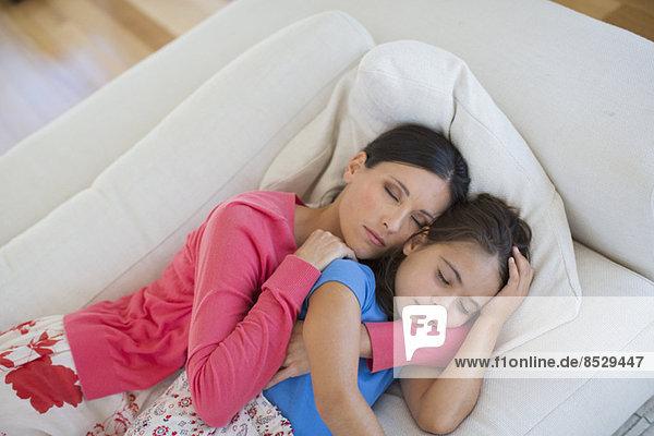 Mutter und Tochter schlafend auf Sofa im Wohnzimmer
