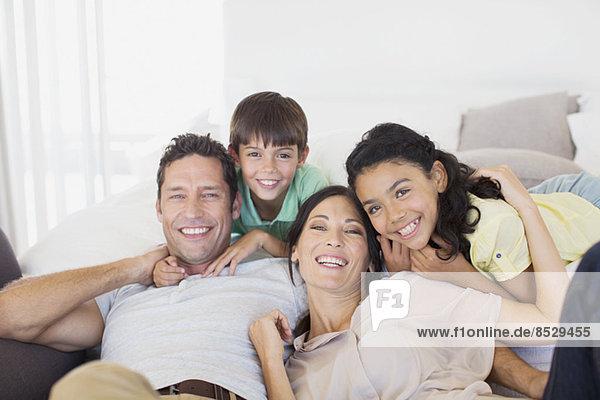 Familie lächelt gemeinsam auf dem Sofa im Wohnzimmer