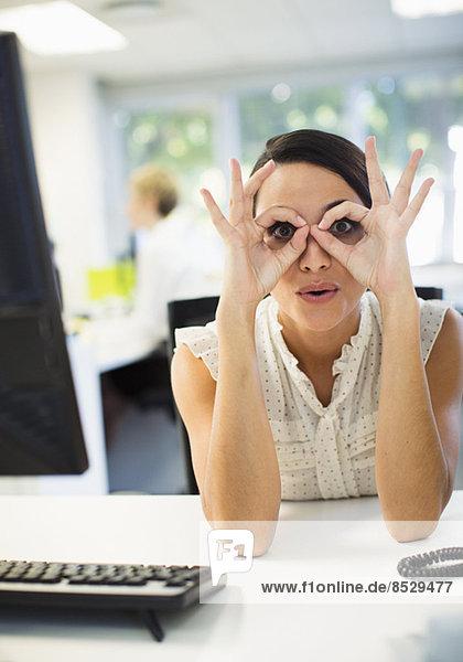Geschäftsfrau macht ein Gesicht am Schreibtisch im Büro