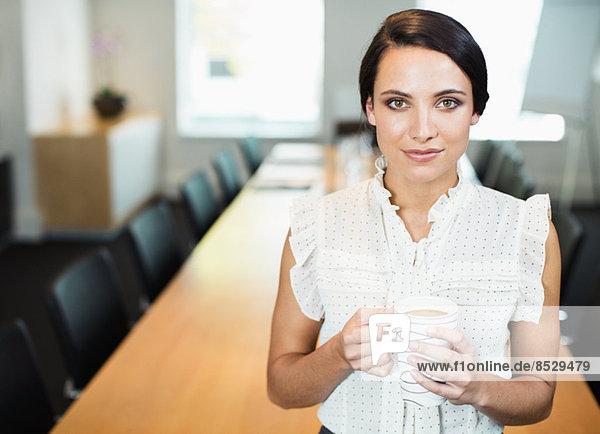 Geschäftsfrau trinkt eine Tasse Kaffee im Konferenzraum