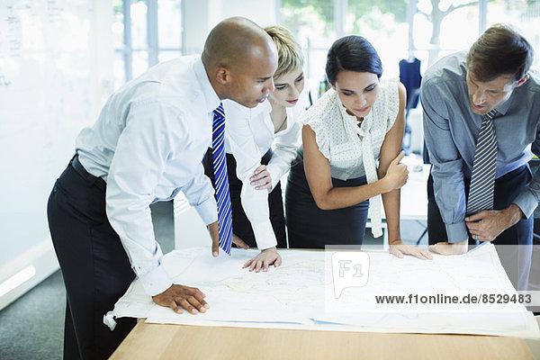 Geschäftsleute bei der Prüfung von Entwürfen im Büro
