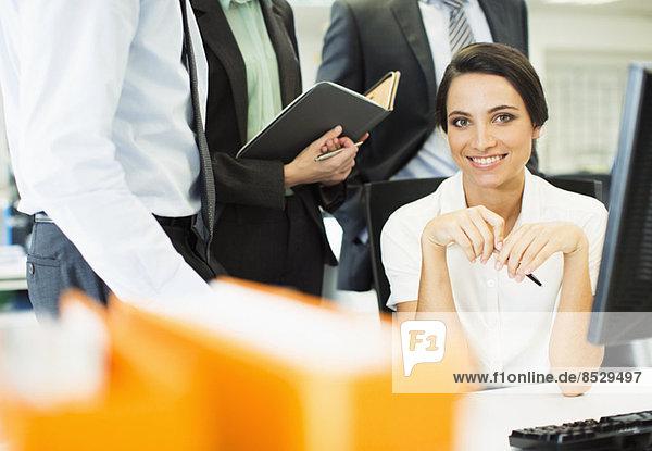 Geschäftsfrau lächelt am Computer im Büro