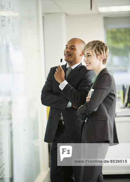 Geschäftsleute betrachten Whiteboard im Büro