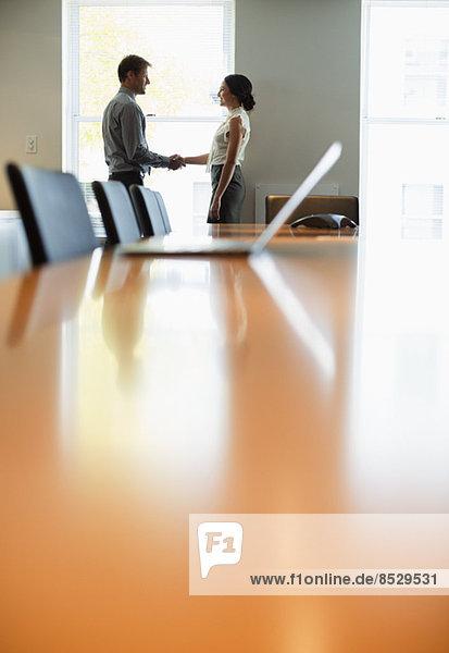 Geschäftsleute beim Händeschütteln im Konferenzraum